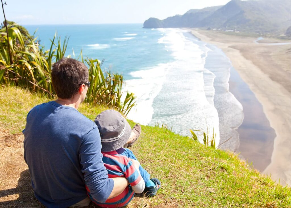A young family looking at the beach in New Zealand. Making a new life in new Zealand