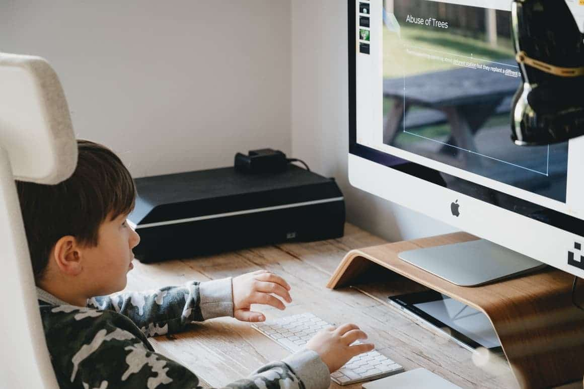Boy playing on computer while homeschooling and his parent is working full time