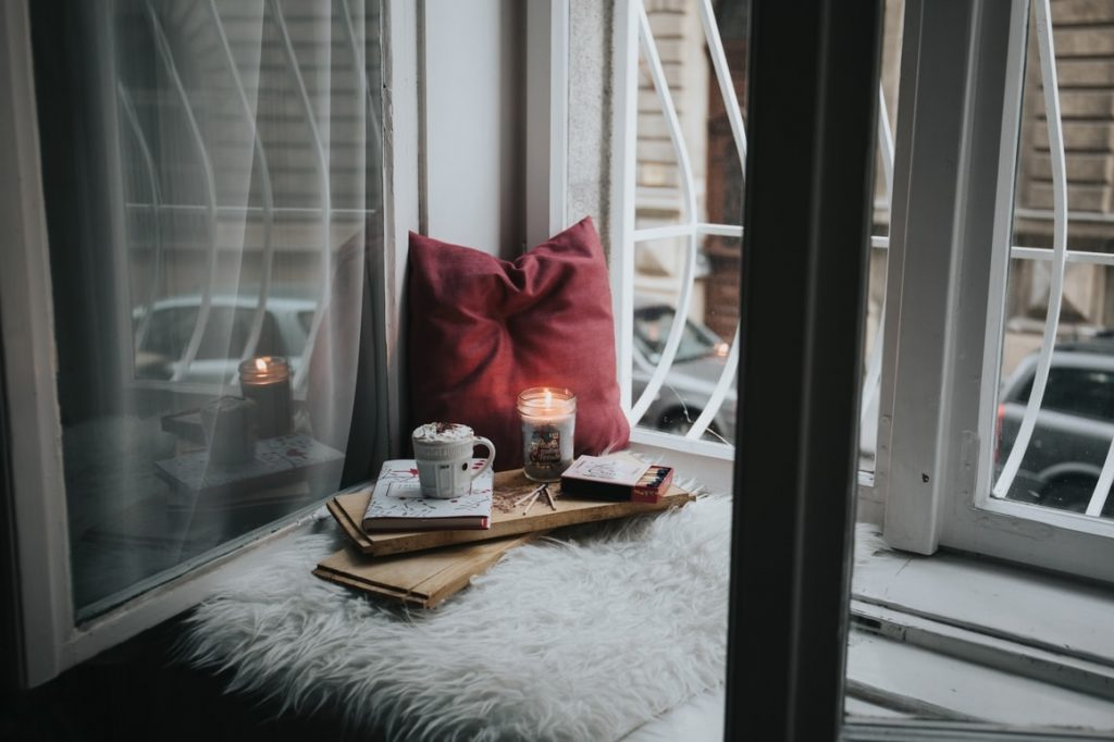 a window seat with a candle, a book and a cup of coffee, Practising self love exercises.