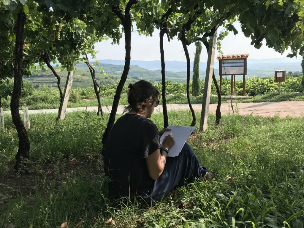 woman writing on a piece of paper under a vineyard. Self love exercises.