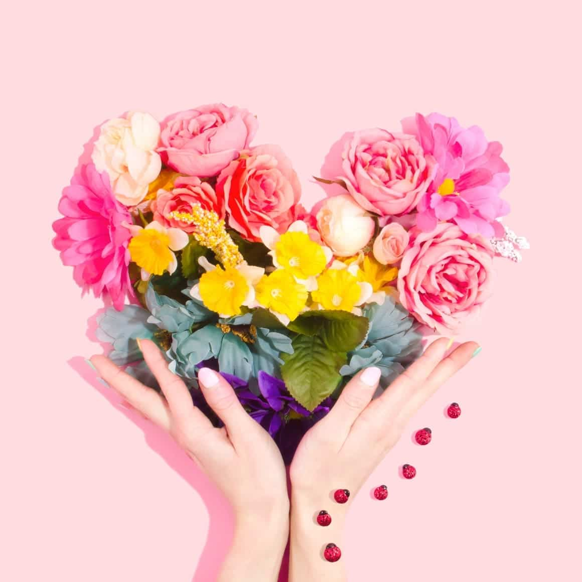 A heart of flowers being held by a womans hand. Self love exercises and why we need them.