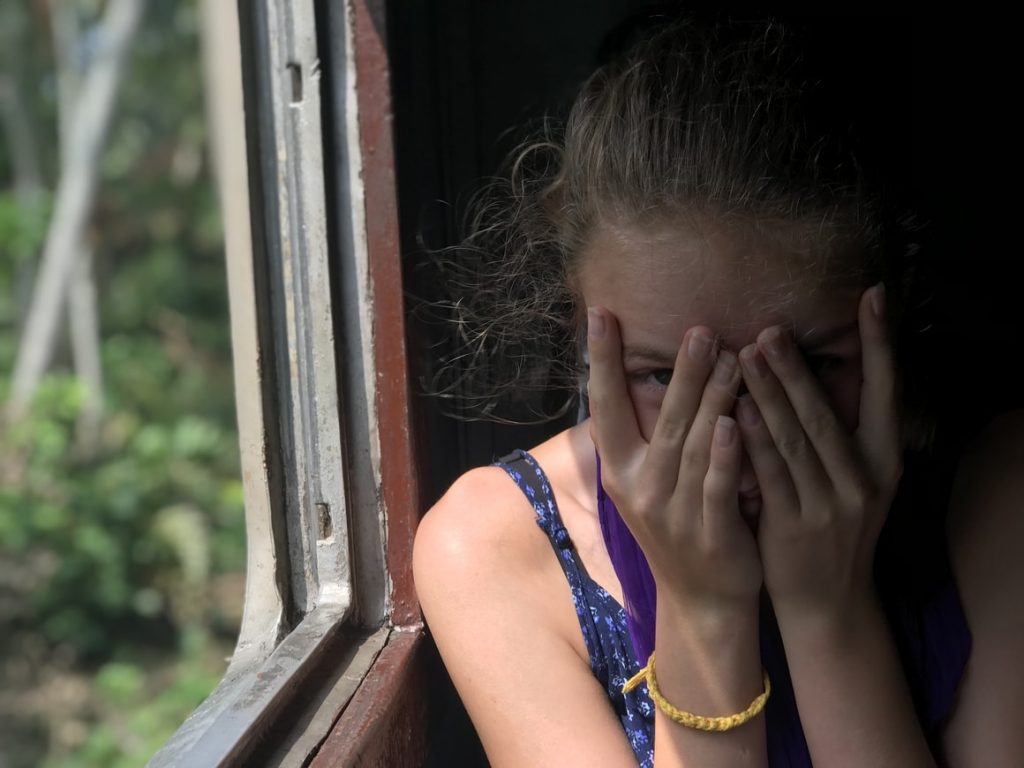 Girl covering her eyes on a train.