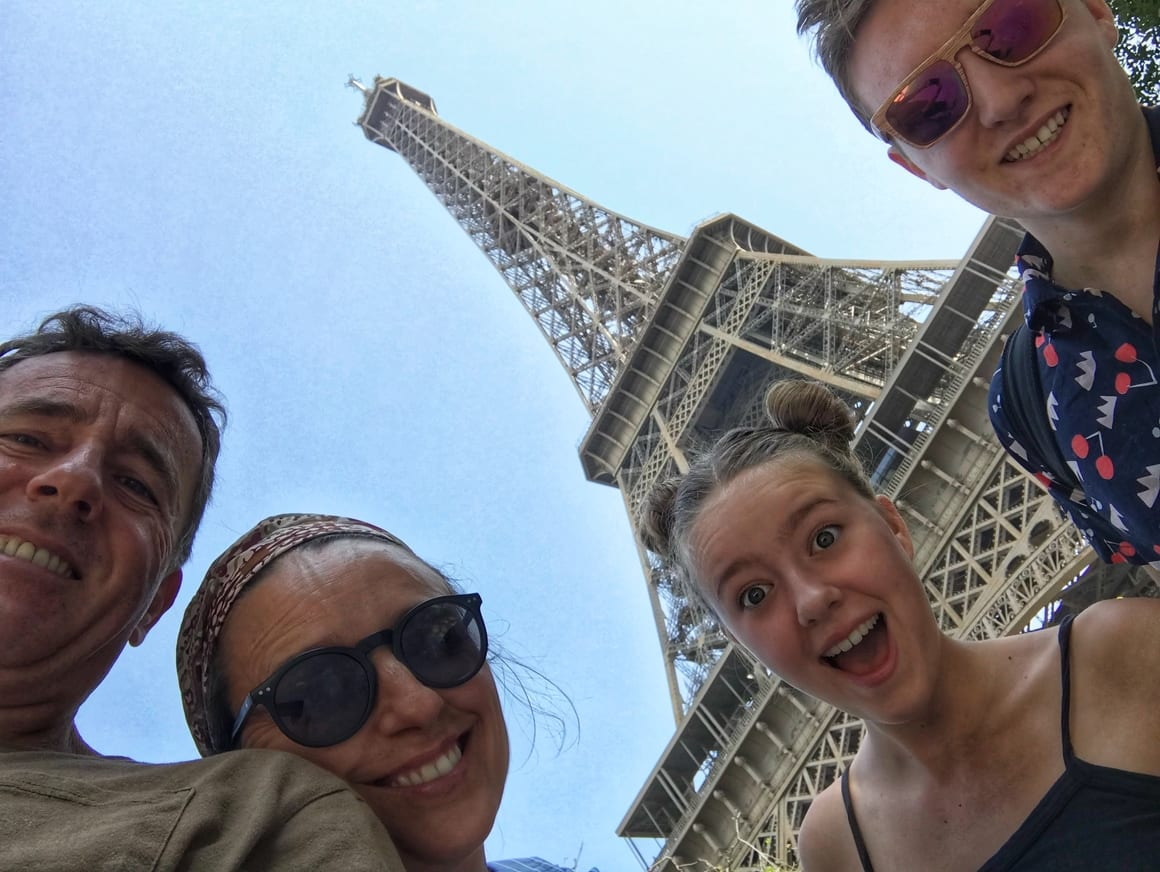 A family standing at the bottom of the Eifell tower. Best European city for kids