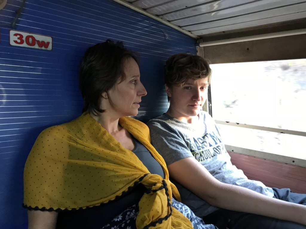 A family travelling in India on a sleeper bus