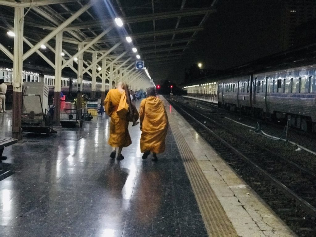 Two monks in Thailand walking alongside the train track. Taking the Bangkok to Chiang Mai train
