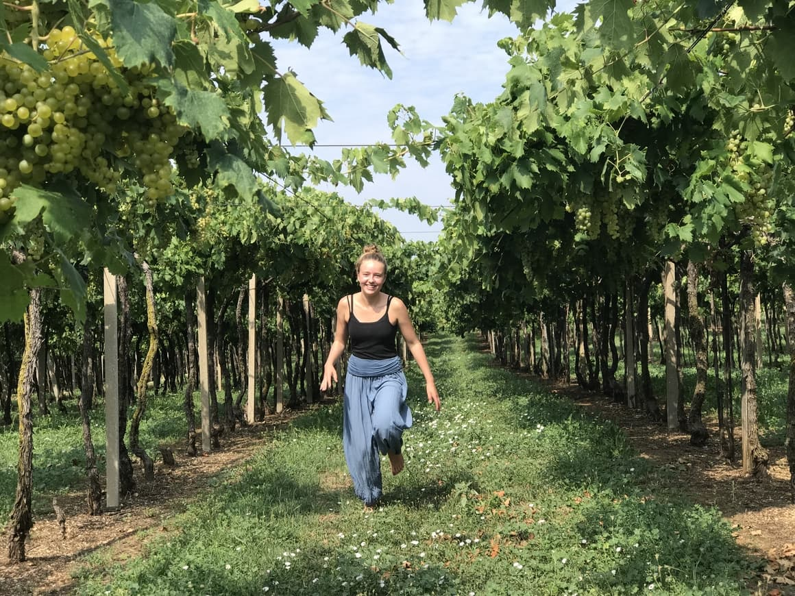 A girl walking through a vineyard in Italy. Italy tips on how to see Italy at its best with kids