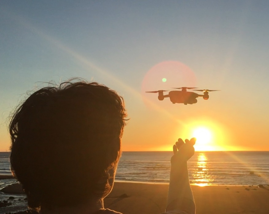 Boy with a drone watching the sunset. Travel checklist for things that you may need for your vacation