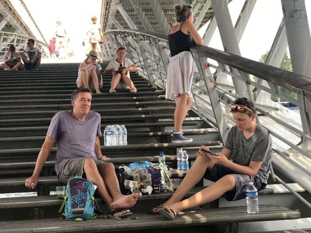 Family having a picnic lunch on the banks of the river Seine in Paris