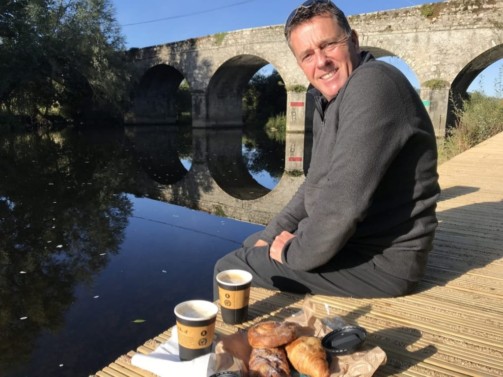 Man sitting by the canal in Ireland drinking coffee. Ireland tips for the first time visitor