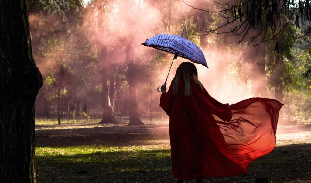 woman standing in the rain with an umbrella and a poncho