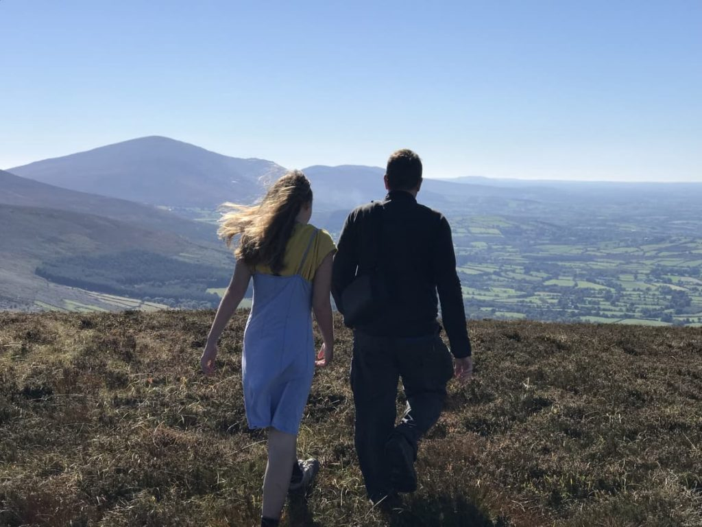 A father and daughter walking on the hills in Ireland. Planning a trip to Ireland