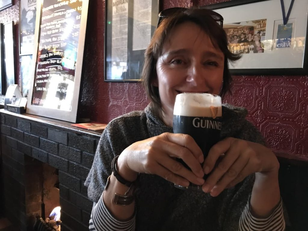 woman drinking Guinness in an Iriish pub. planning a trip to Ireland