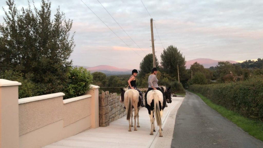 two women on horseback on the roads of ireland countryside. Planning a trip to Ireland