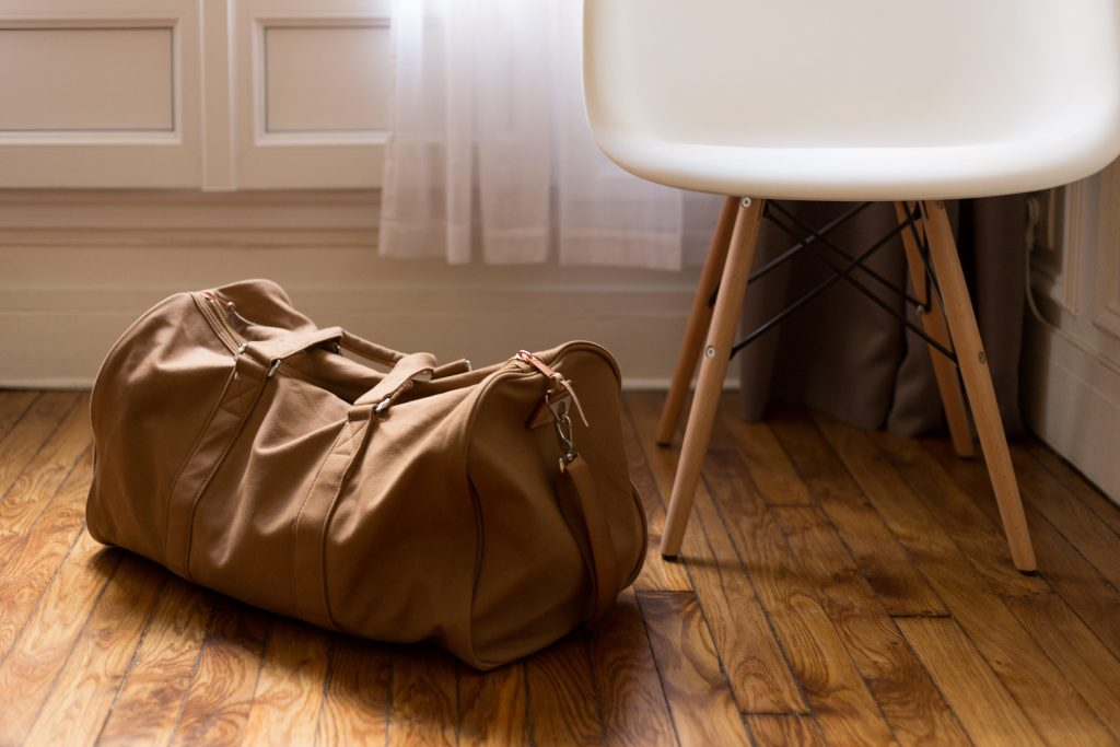 a duffle bag by a chair