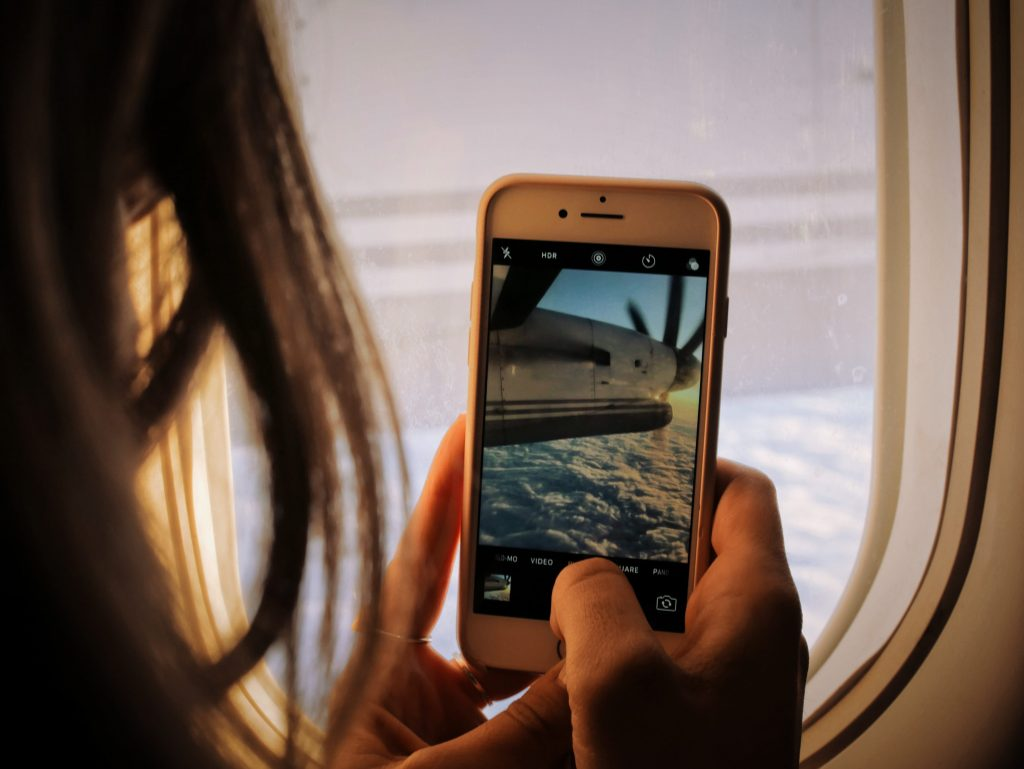 girl taking a photo on her mobiile phone out of a plane window