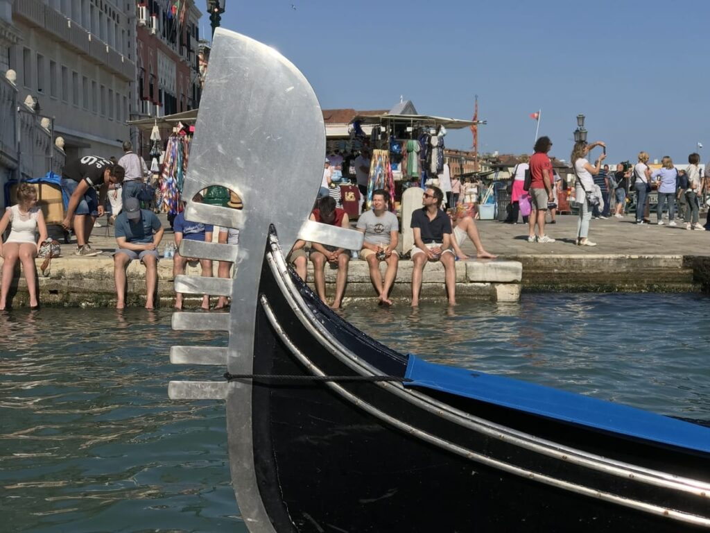 Tourists putting their feet in the water in Venice