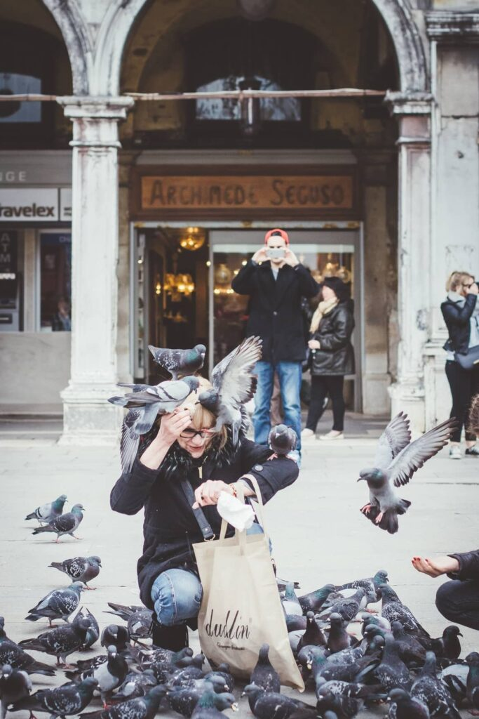 Woman feeding the pigeons in Venice