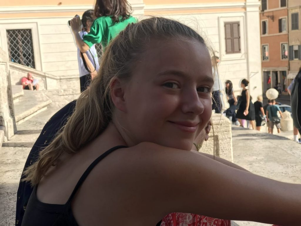 Girl with sunburn sitting in Italy