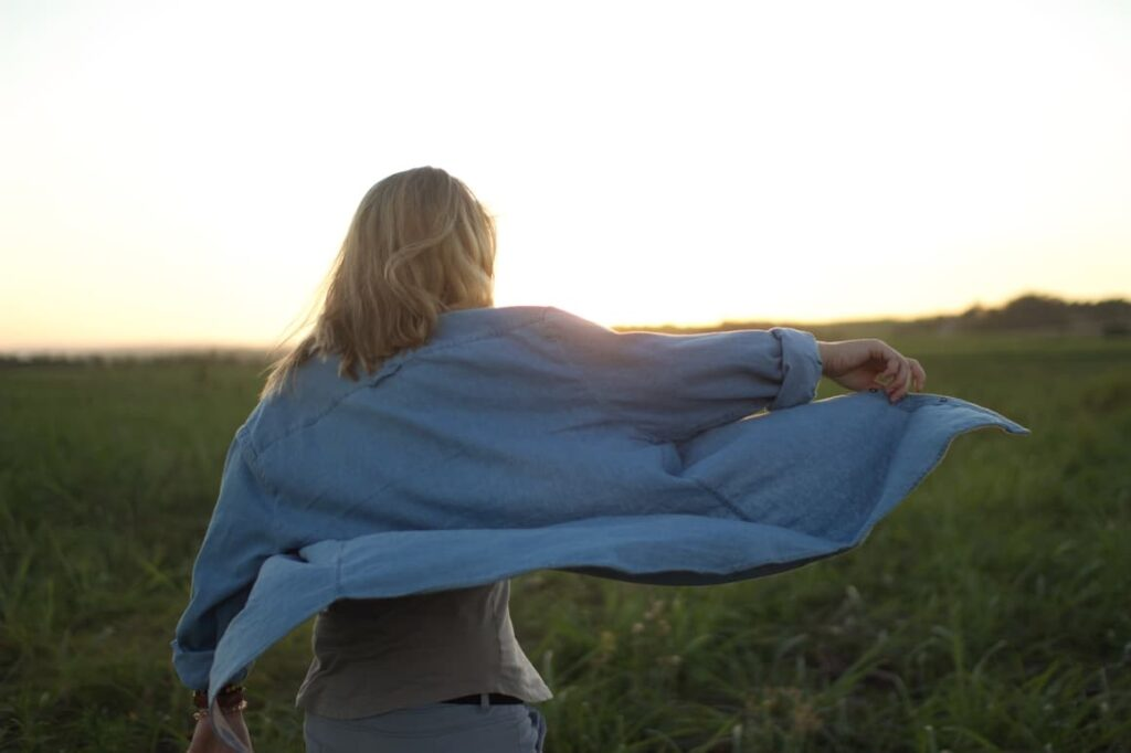 Woman walking in a field feeling free after being off social media for a few days