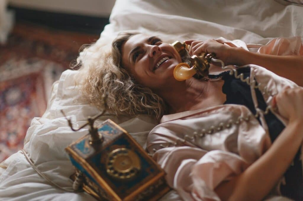 Woman laying on the bed chatting on a telephone