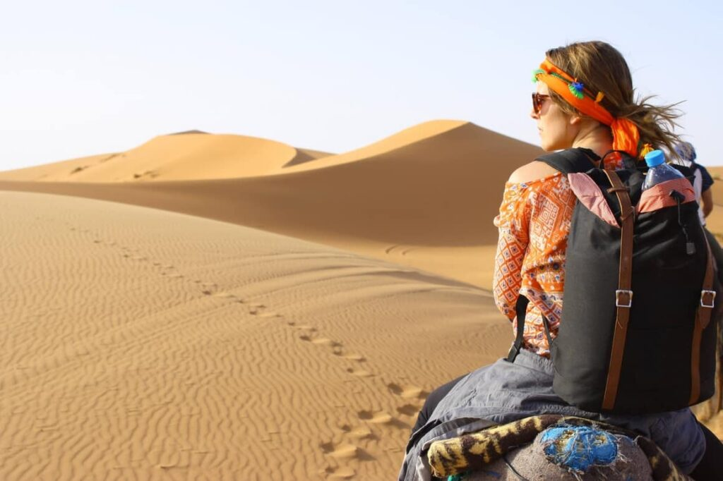 woman on a camel in the desert.Travel essentials