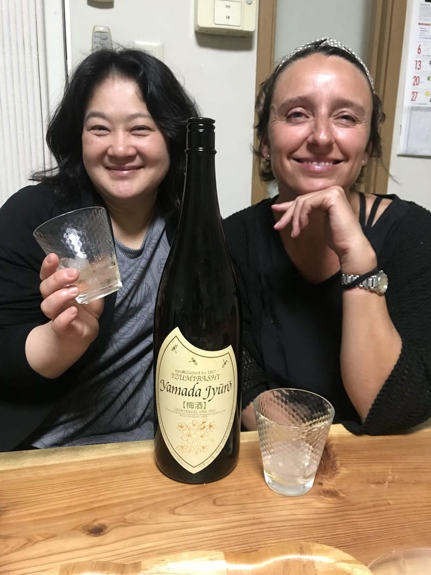 A Western woman with a lady from Japan drinking wine and learning about Japanese culture facts