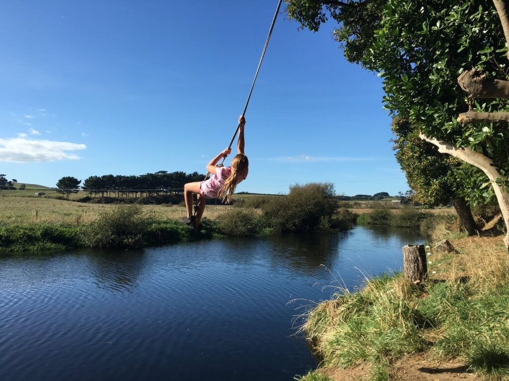 Girl swinging over water in new Zealand