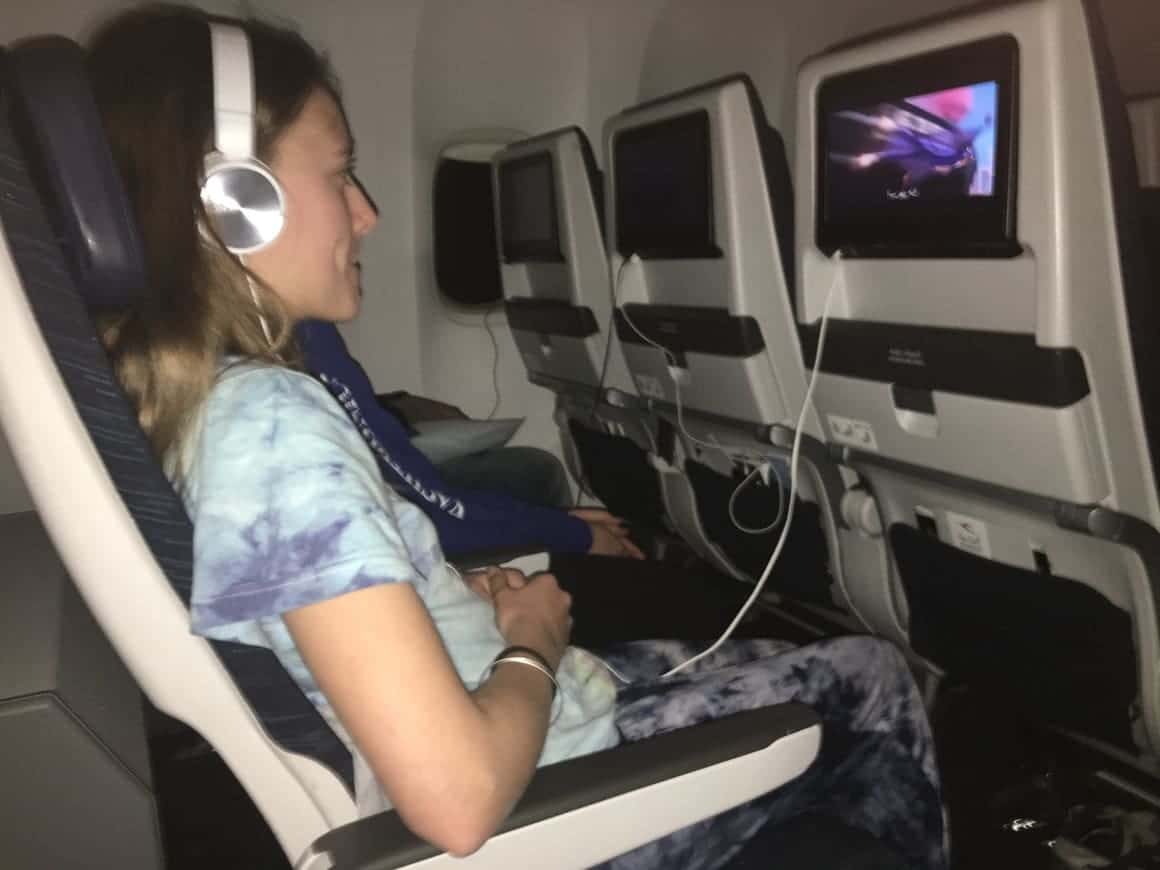 A girl on a airoplane trying to get sleep to avoid getting jet lag