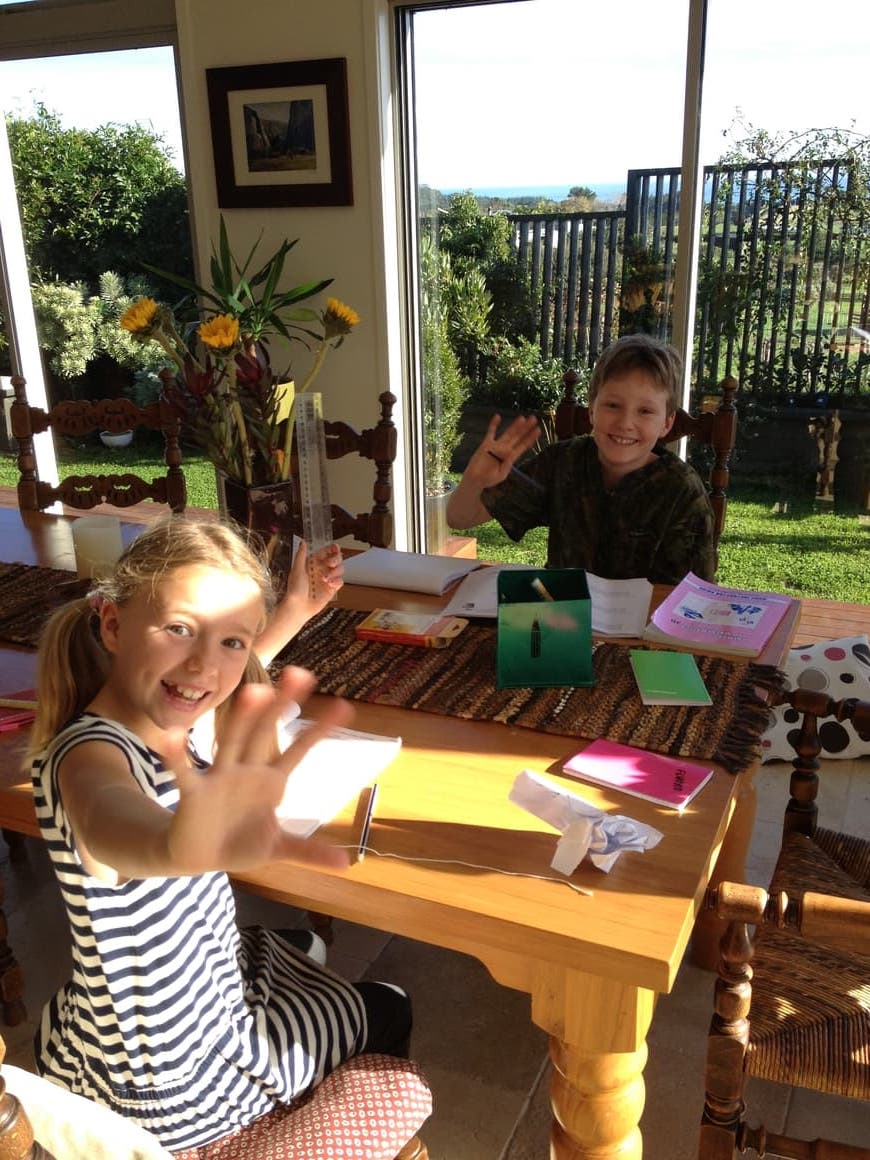 Kids homeschooling at a table.