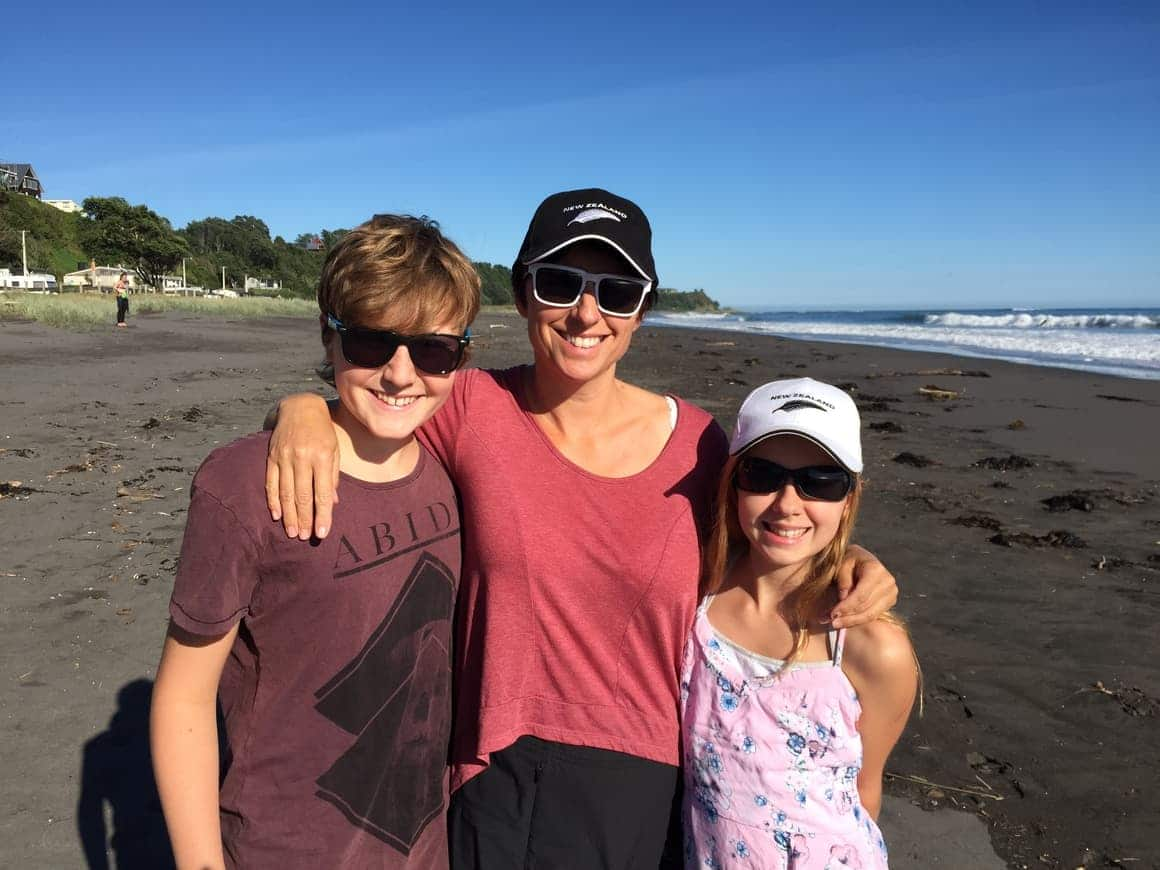 A homeschooling family standing on the beach