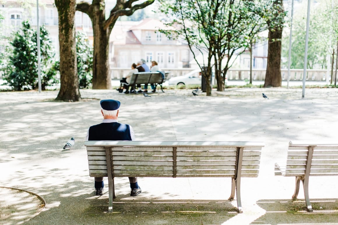 An old man sitting at a bench