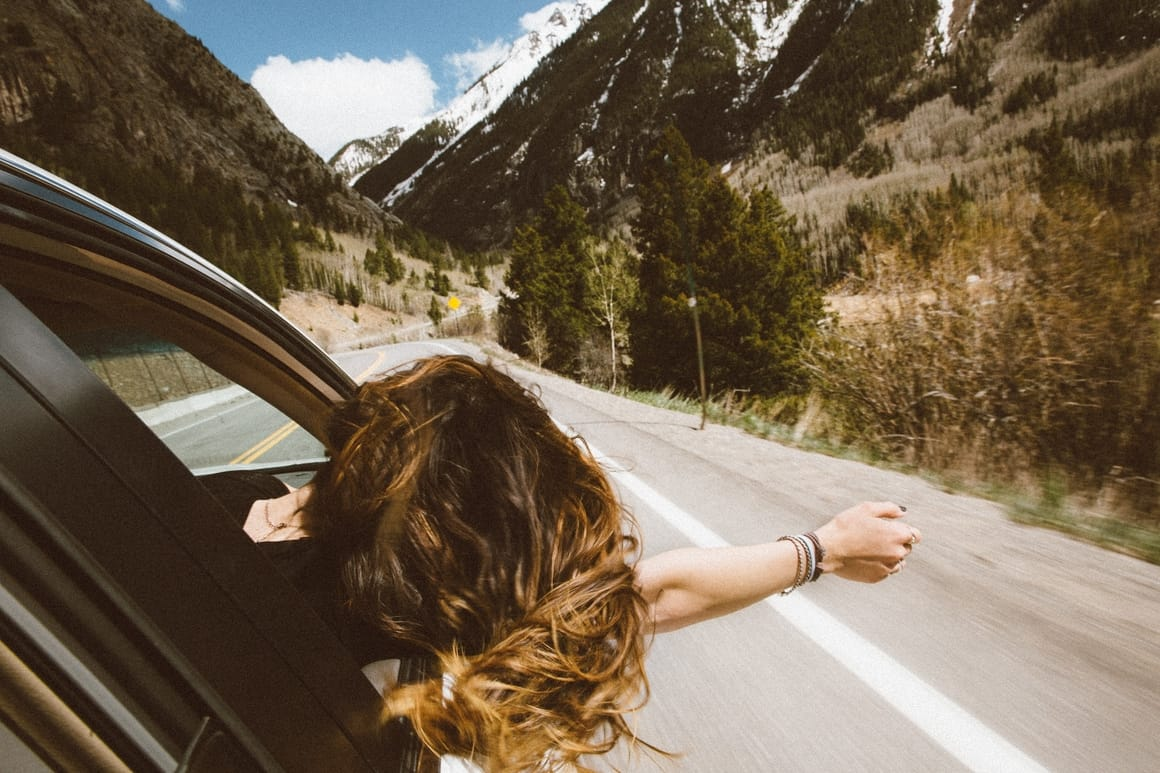 Woman in a car taking a road trip
