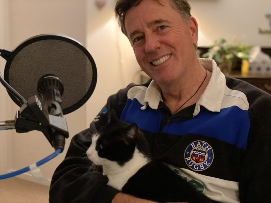 Man with a cat on his knee chatting on the new Zealand podcast