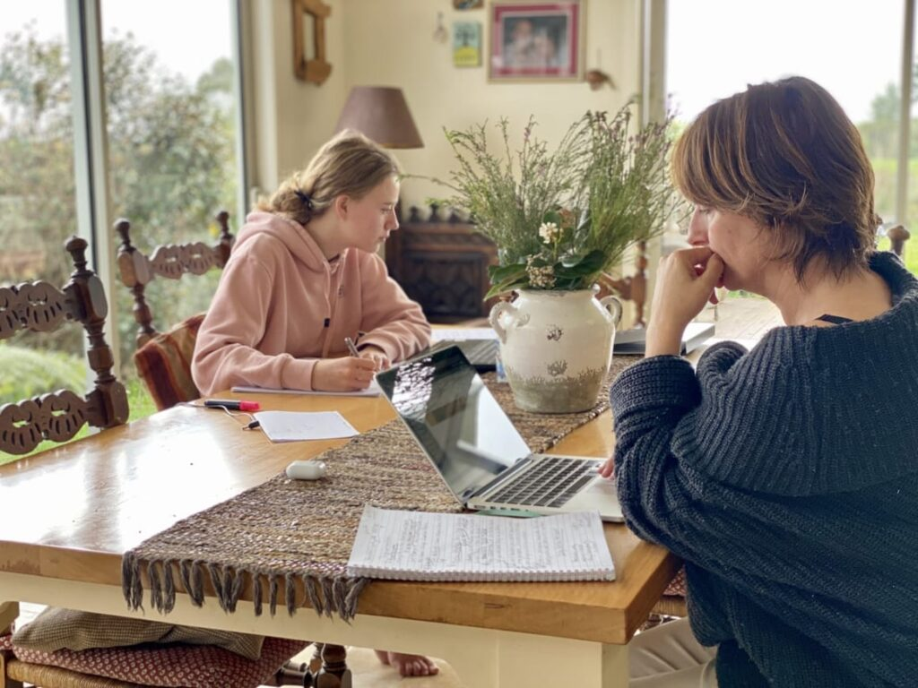 Mother and daughter homeschooling and working at the same time