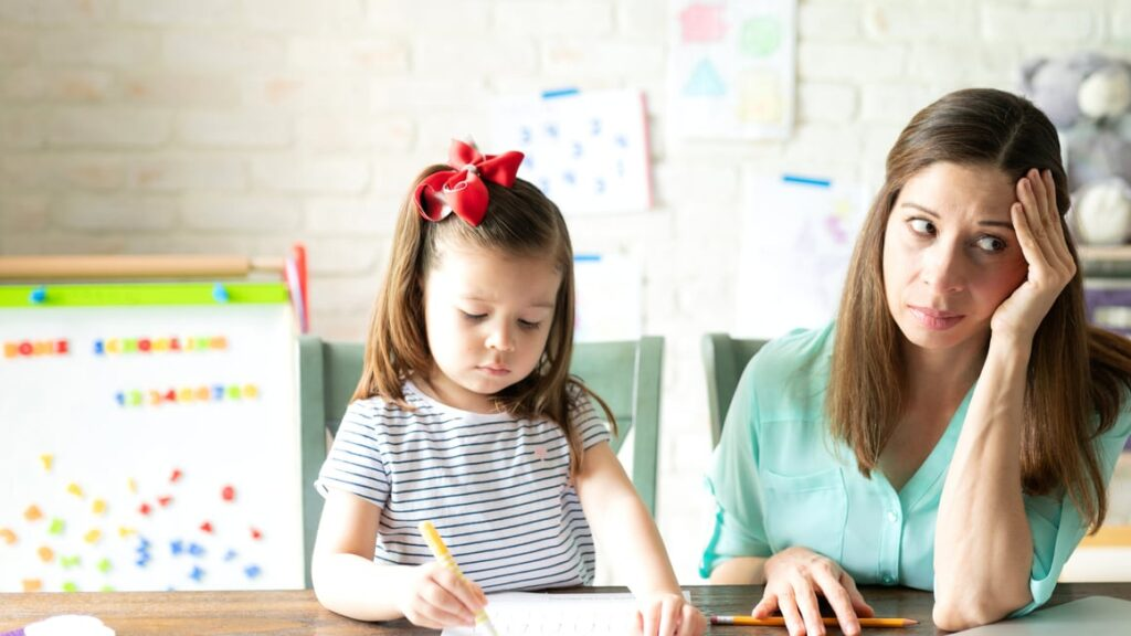 Woman looking stressed while teaching her daughter at home