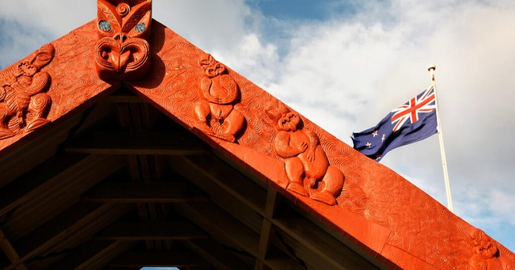 Māori Carving in front of a New Zealand flag.