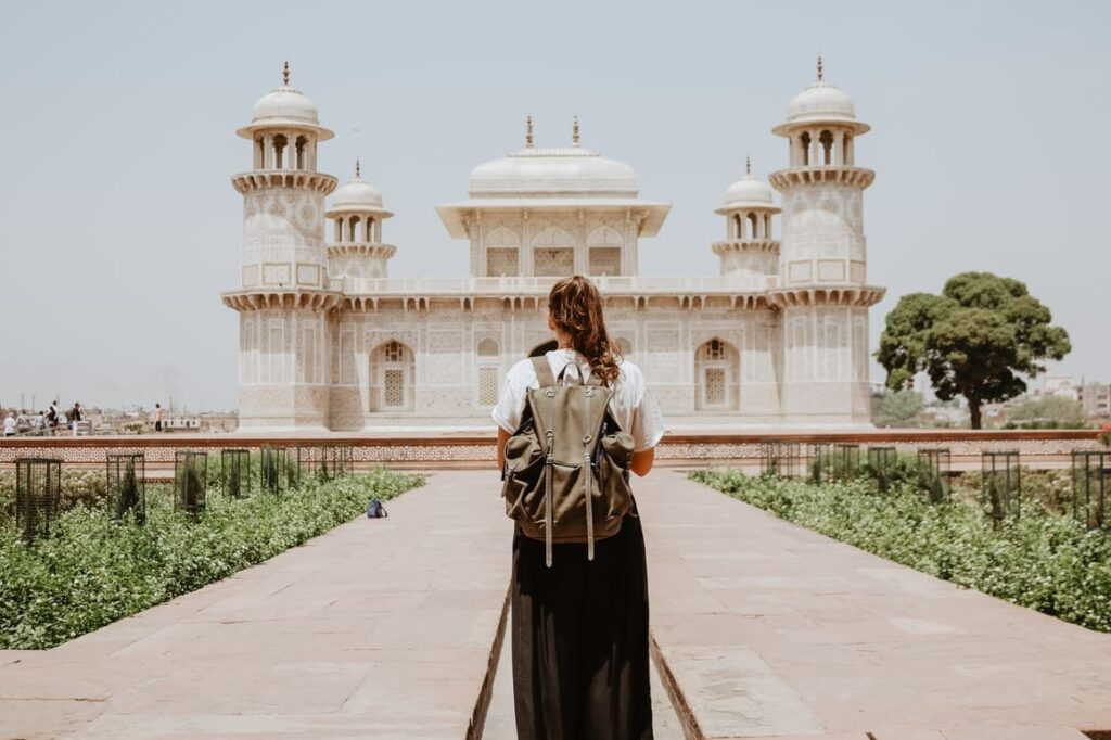 Girl standing infront of a an Indian building.