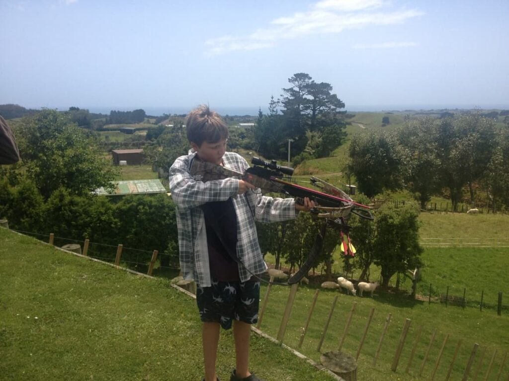 Boy shooting a bow and arrow in New Zealand