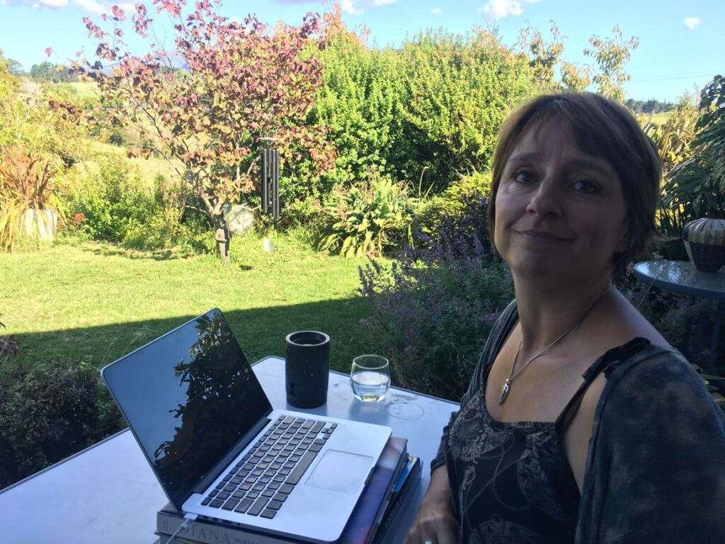 Woman working from home on her computer out side in the garden