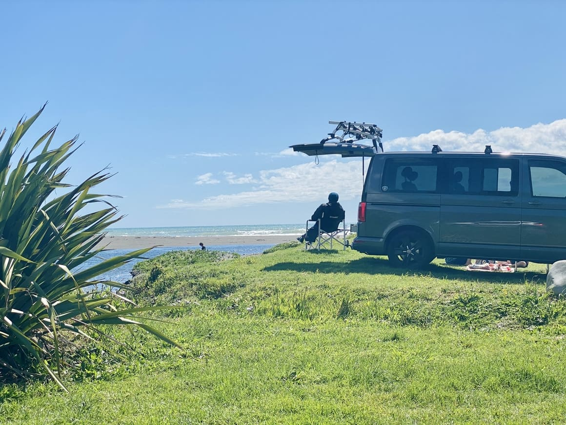 A woman sitting outside her motorhome in New Zealand