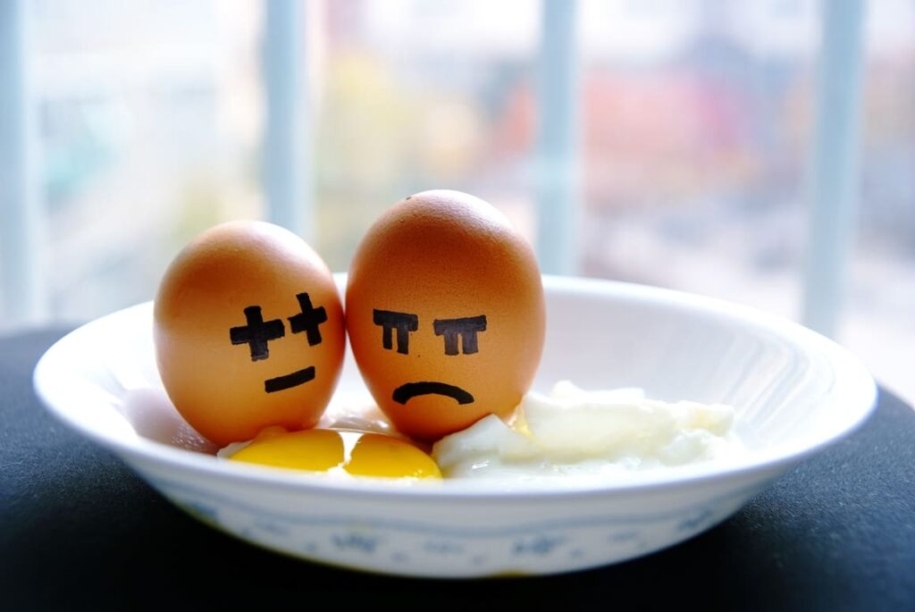 Two eggs with angry faces drawn onto them