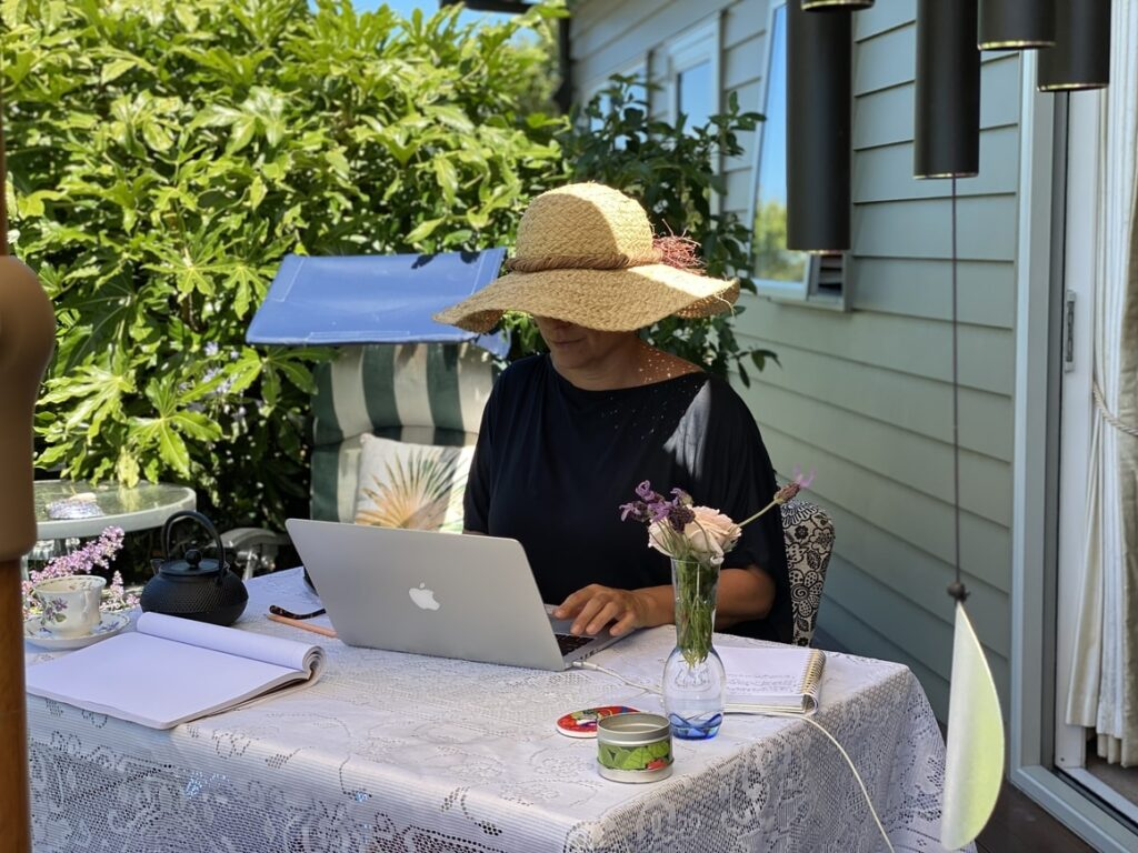 Woman in a hat. Writing a book outside in the garden on a computer