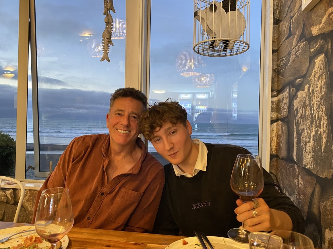 Man with teenage son at a restaurant in New Zealand