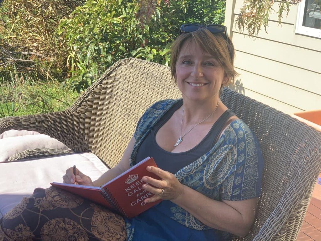 A woman sat on a bench Writing a book